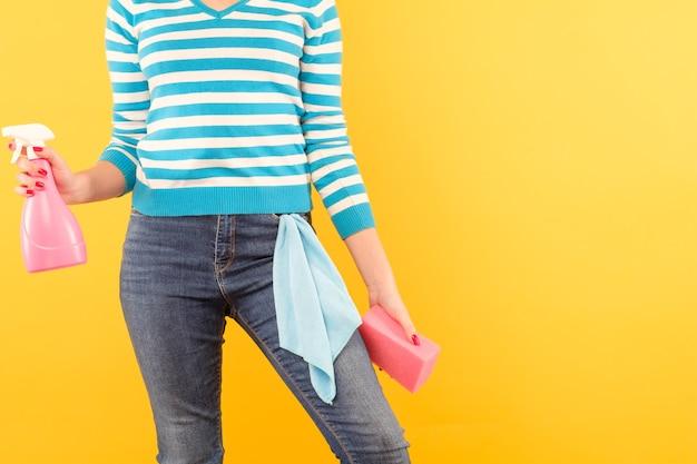 窓拭き。家事。ポケットに布でアトマイザーとスポンジを保持している女性。黄色い壁のスペースをコピーします。