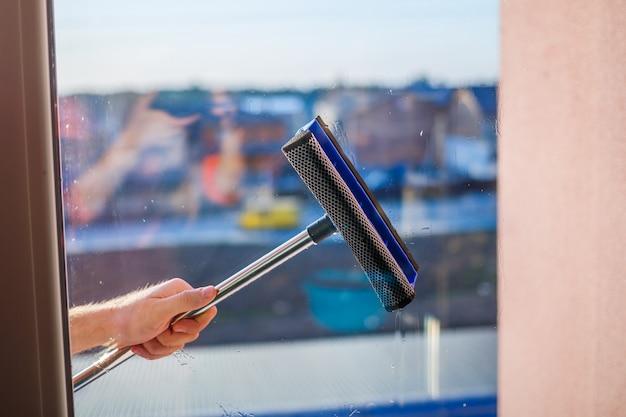 Мытье окон в многоэтажках, домах щеткой. щетка для мытья окон. большое окно в многоэтажном доме, уборка. удаление пыли и мойка стекла.