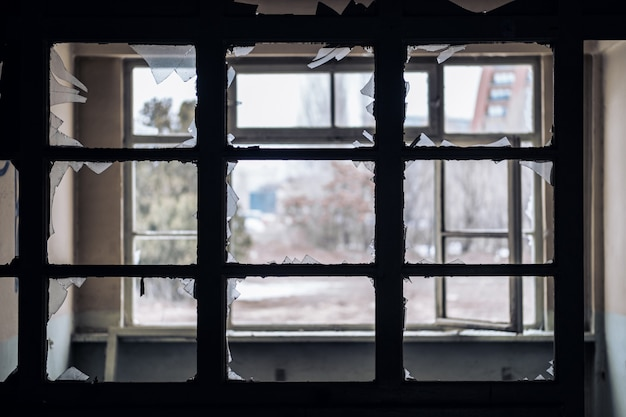 Window of an empty abandoned old building with broken glasses
