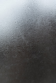 Window glass with water drops. abstract gray surface with drops and stains. vertical frame.