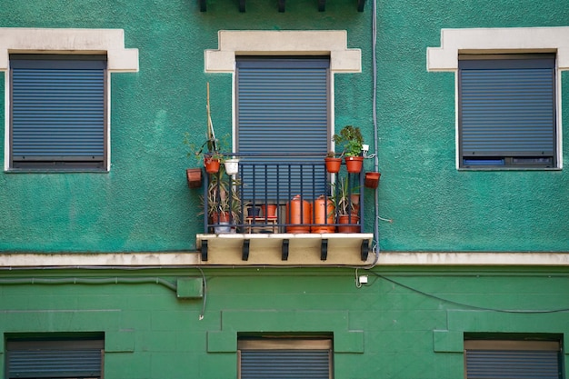 Window on the green facade of the house in the city