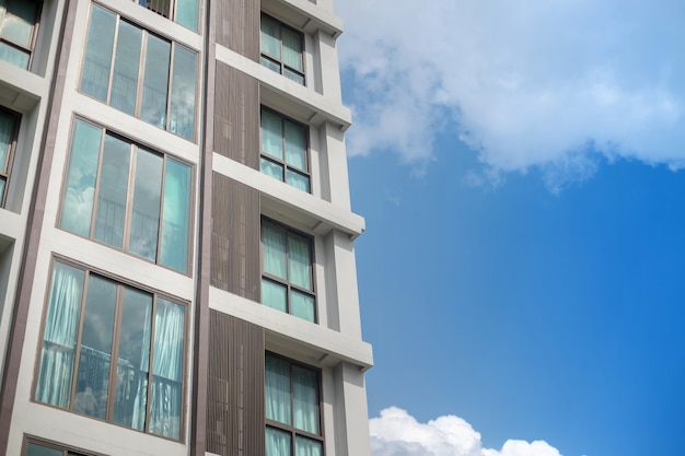 白い雲青い空を背景に近代的なマンションの建物の窓グリッド