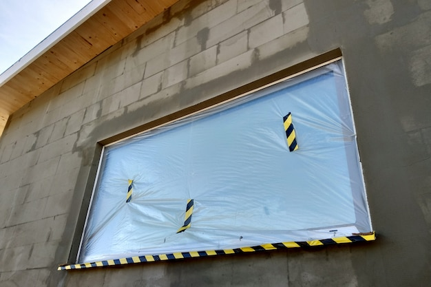 Window of a house under construction covered with protective plastic film.
