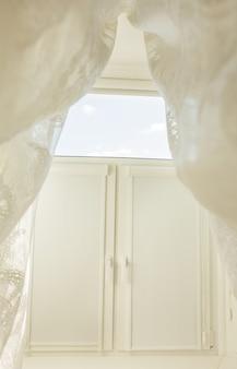 투명한 얇은 명주 그물과 닫힌 롤 커튼이있는 침실의 창. 화창한 날 아침에 찍은 사진