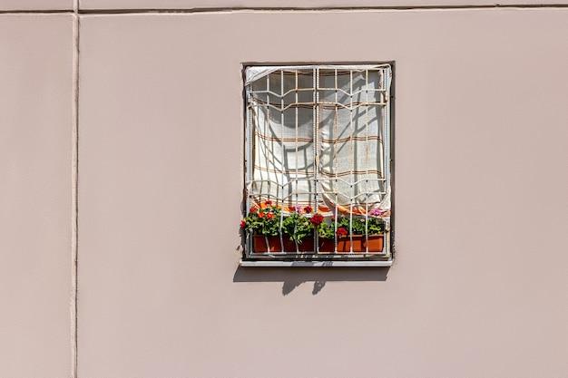 직사광선으로부터 보호하기 위해 수건으로 덮인 집의 창. 여름 더위에 아파트를 냉각하는 저렴한 방법