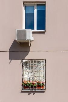 직사광선 대 에어컨 시스템으로부터 보호하기 위해 수건으로 덮인 집의 창. 여름 더위에 아파트를 냉각하는 저렴한 방법