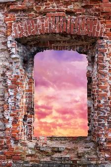 Окно в кирпичную стену с видом на закатное небо. фото высокого качества