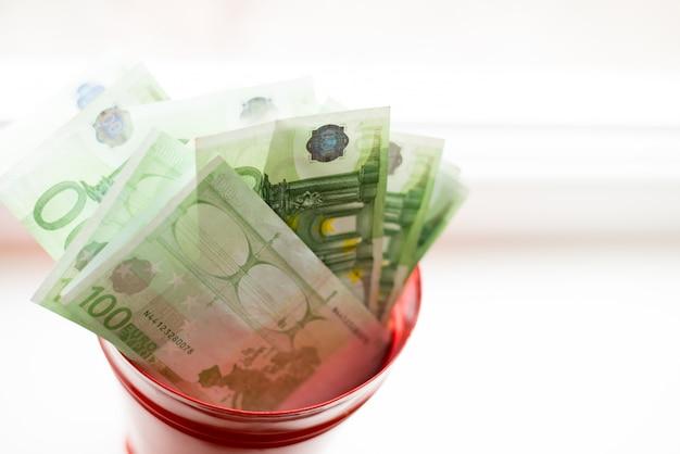 貯金箱、白いwindow.light背景にバケツでユーロ紙幣