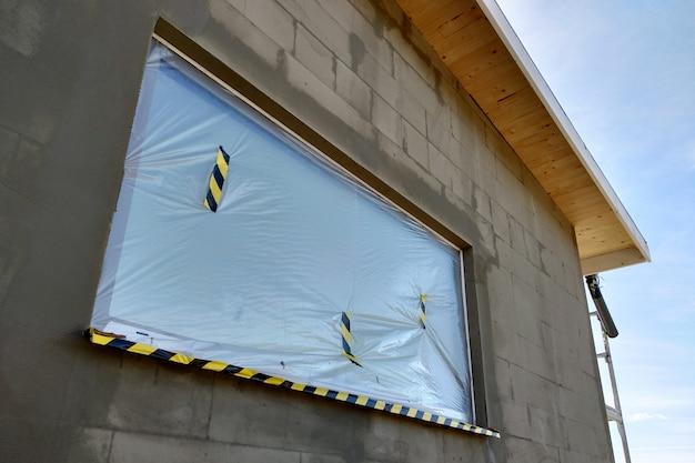 Окно строящегося дома покрыто защитной пластиковой пленкой.