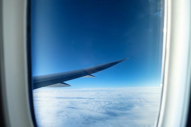 青い空に白い雲と航空機の翼の窓