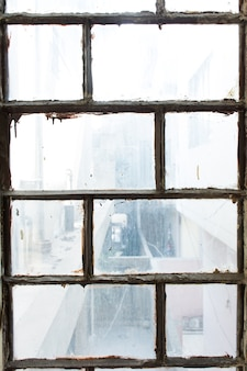 Window of an old house inside view rusted and damaged