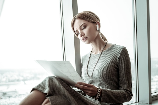 On window sill. busy concerned smart businesswoman sitting on window sill preparing for meeting