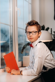 At the window stands a boy in a shirt with a red bow tie and glasses, holding a red book in his hands.