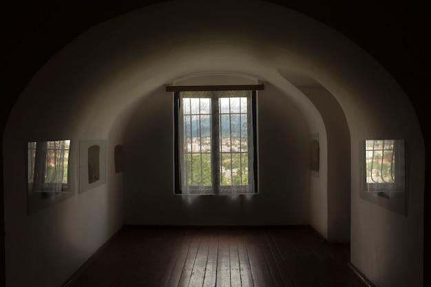 어두운 방의 아치형 창에 격자가 있는 창