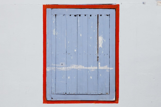 Window with blue shutters on a white wall.