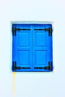 전통적인 파란색으로 칠해진 닫힌 셔터가 있는 창, 그리스 산토리니