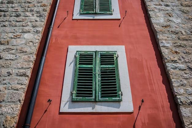 Окно с закрытыми деревянными ставнями в старом каменном городе