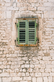 A window with green closed wooden shutters in the brick wall of an old house