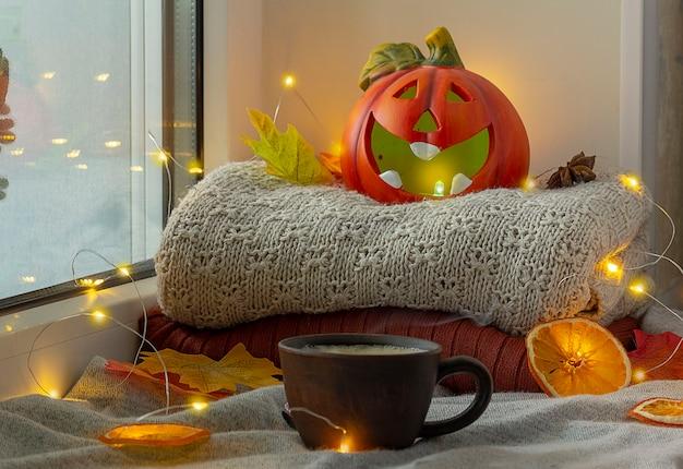 Окно с украшением хэллоуина. тыква со свечой. рядом стоит чашка горячего кофе.