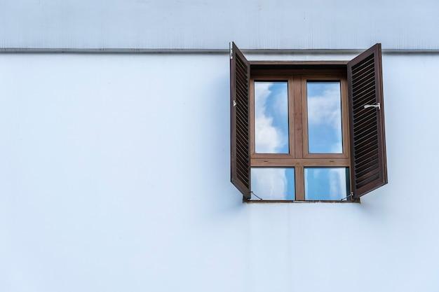 Окно с деревянными ставнями на белой штукатурке стены и копией пространства. остров занзибар, танзания, восточная африка