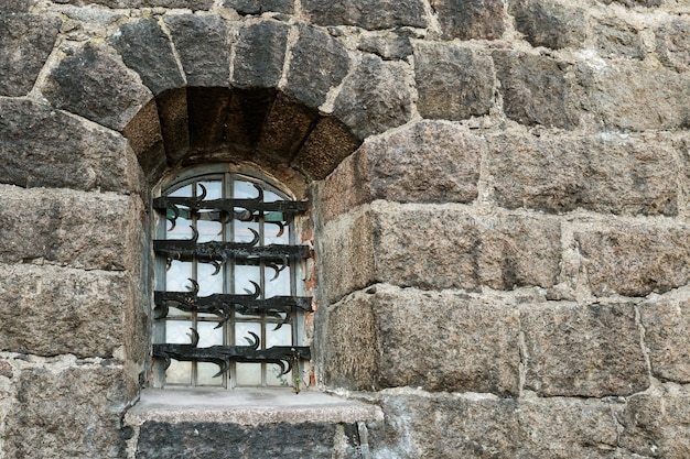 Window with wrought iron grille on dark stone wall