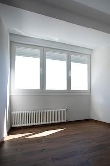 木製の床とガスラジエーター付きの窓付きの部屋