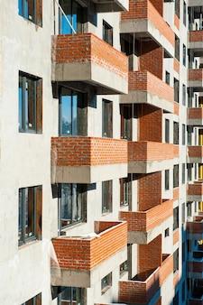 Окна и балконы из кирпича строящегося нового дома. монолитное строительство