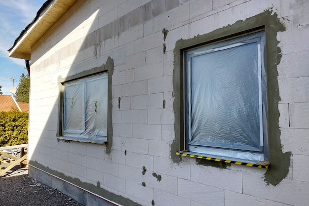 Windows of a house under construction covered with protective plastic film.