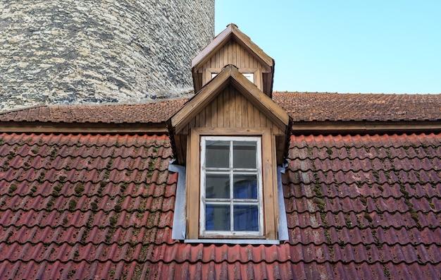 非常に古い中世の家の傾斜した屋根の窓。