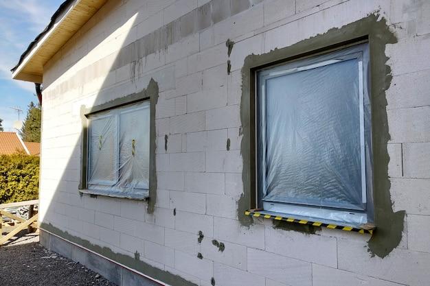 Окна строящегося дома покрыты защитной пластиковой пленкой.