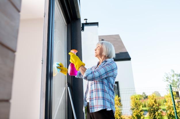 外の窓。彼女の夏の家の外で窓を洗う青い四角いシャツを着ている年配の主婦