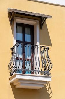 Окна с балконом на фасаде здания с чугунными украшениями в бодруме, турция