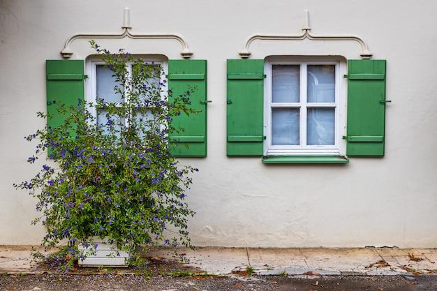 바바리아, 독일에있는 전통적인 오래 된 흰색 건물에 녹색 셔터가있는 창