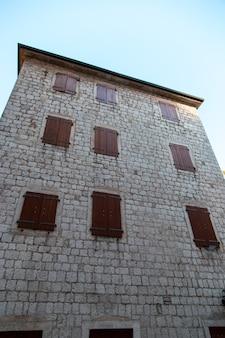 Окна со ставнями на старый каменный дом, старинная архитектура.