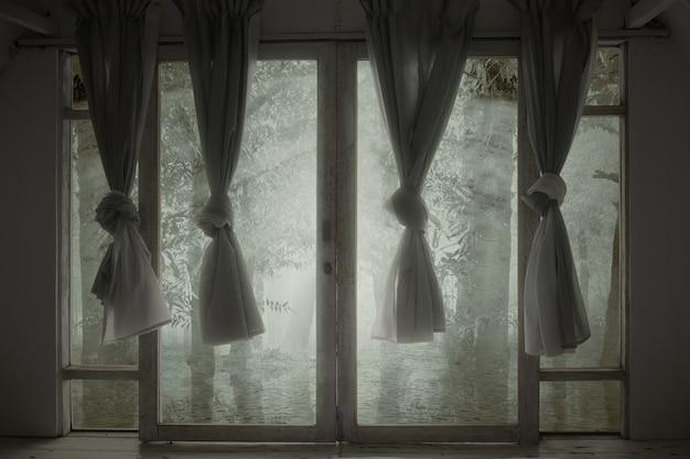 유령의 숲이있는 버려진 집에 커튼이 달린 창문