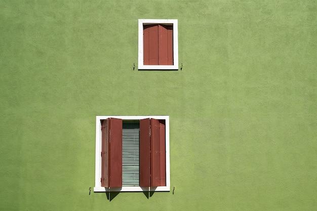 Windows с коричневой штаркой на зеленой стене. италия, венеция, остров бурано.