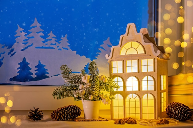 On the windowsill, among the christmas tree decorations, a night light in the form of an old european house glows near a night snow window and paper decorations.