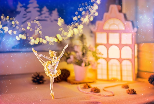 On the windowsill, among the christmas tree decorations, a night light in the form of a village house glows of a night snow window and paper decorations.