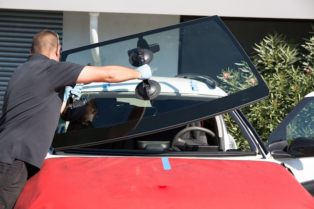 Windshield replacement, man is changing windscrenn on a car