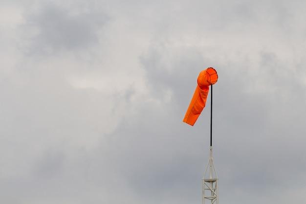 Ветроуказатель против голубого неба и облаков