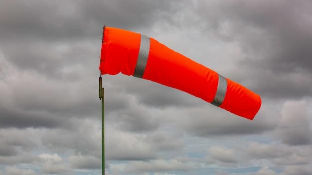 바람 방향과 힘을 나타내는 탱크 화학 원뿔에 바람의 windsock 표시기. 백그라운드에서 구름 하늘과 수평으로 비행 windsock (풍향).