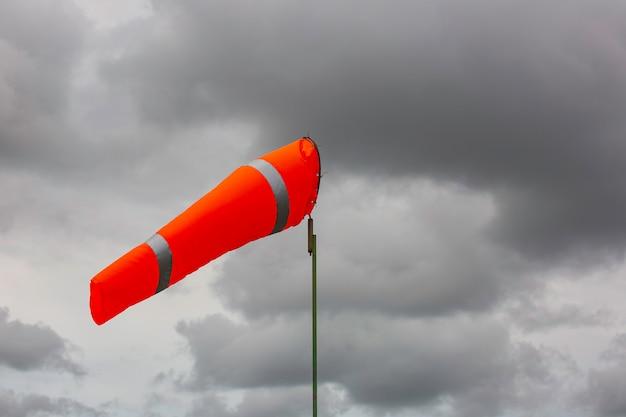 風向と風力を示すタンクケミカルコーン上の風の吹流しインジケーター。雲の空を背景に水平に飛ぶ吹流し(風見鶏)。