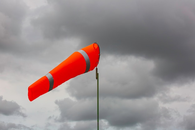 Windsock indicator of wind on tank chemical cone indicating wind direction and force. horizontally flying windsock (wind vane) with cloud sky in the background.
