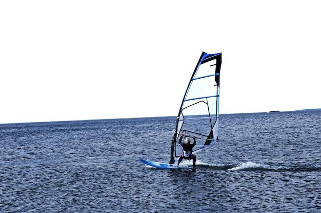 Виндсерфер быстро скользит по синему морю с копией пространства