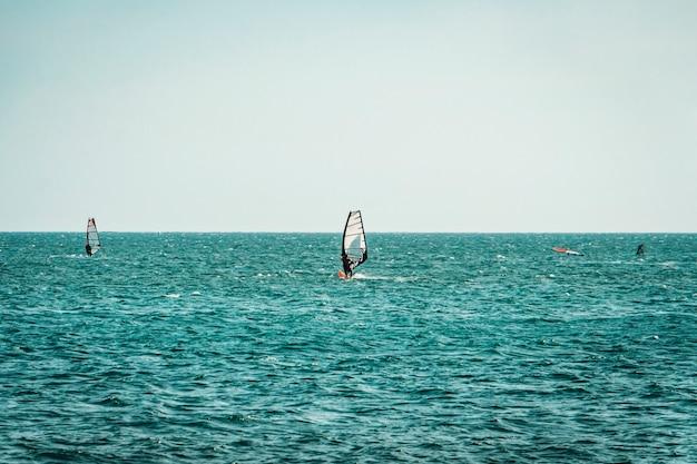 ベトナムのムイネーで波に乗って風をサーフィンするウィンドサーファー。レクリエーションウォータースポーツ、エクストリームスポーツアクション。レクリエーションスポーツ活動。健康的なアクティブライフスタイル。夏の楽しい冒険。趣味。