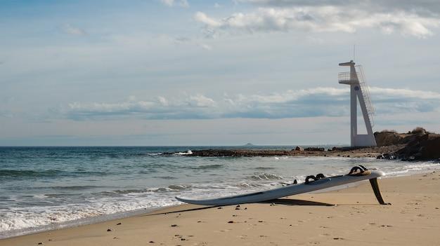 海の波でサーフィンの準備ができてビーチに横たわっているウィンドサーフィンボード