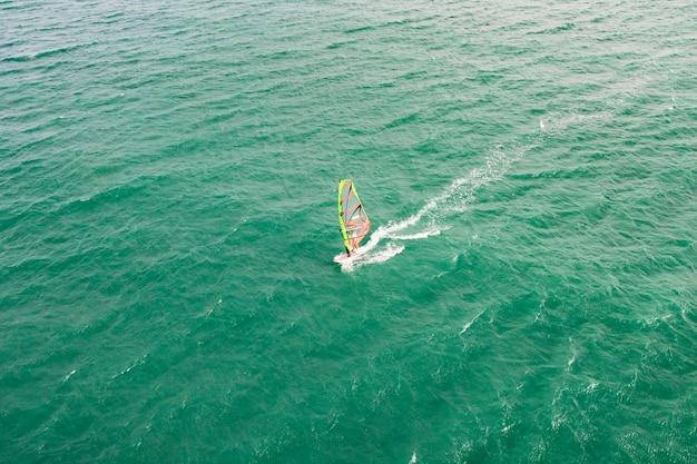 ウィンドサーフィン、ウィンドサーフィン。トロピカルブルーの海、澄んだ水でのエクストリームスポーツ。空撮、ベトナムの美しい海の波、ムイネーでのウィンドサーフィンの平面図。