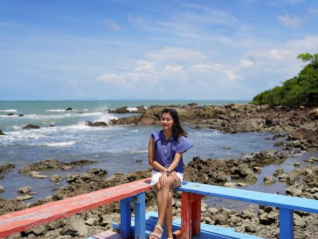 風の強い髪の女性観光客の女性は、タイ、チャンタブリーのバンフアレムで岩のビーチの海の景色と明るい青空の赤と青の木製シートテラスコーナーに座っています