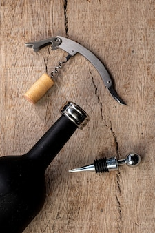 Набор принадлежностей для вина, со штопором, кольцом и крышкой от винной бутылки, вид сверху на деревенском дереве.