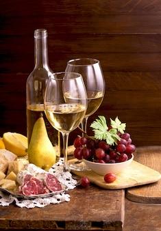 木製のテーブルの上のヴィンテージの設定でワインとブドウ
